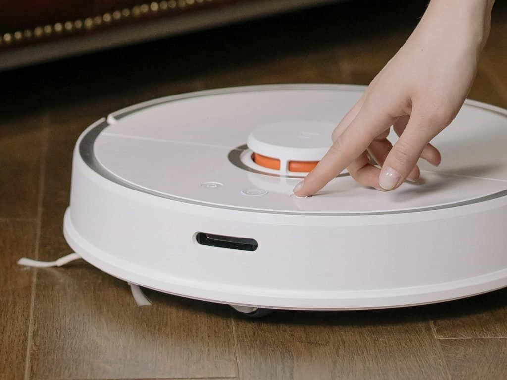 Picture showing a hand operating a robotic vacuum cleaner