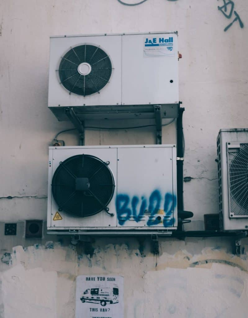 dirty air conditioners on grungy building wall
